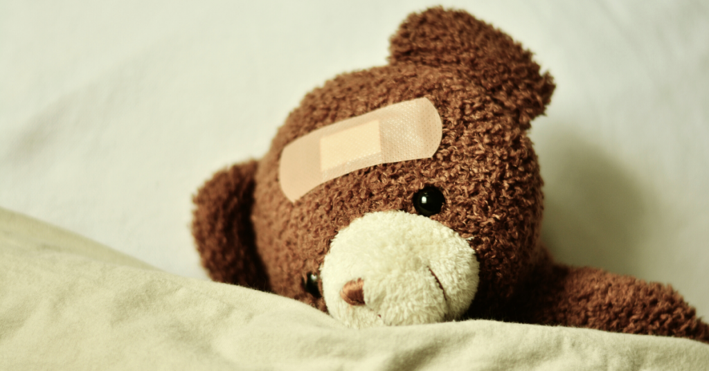 Teddy bear on the bed with a bandaged head