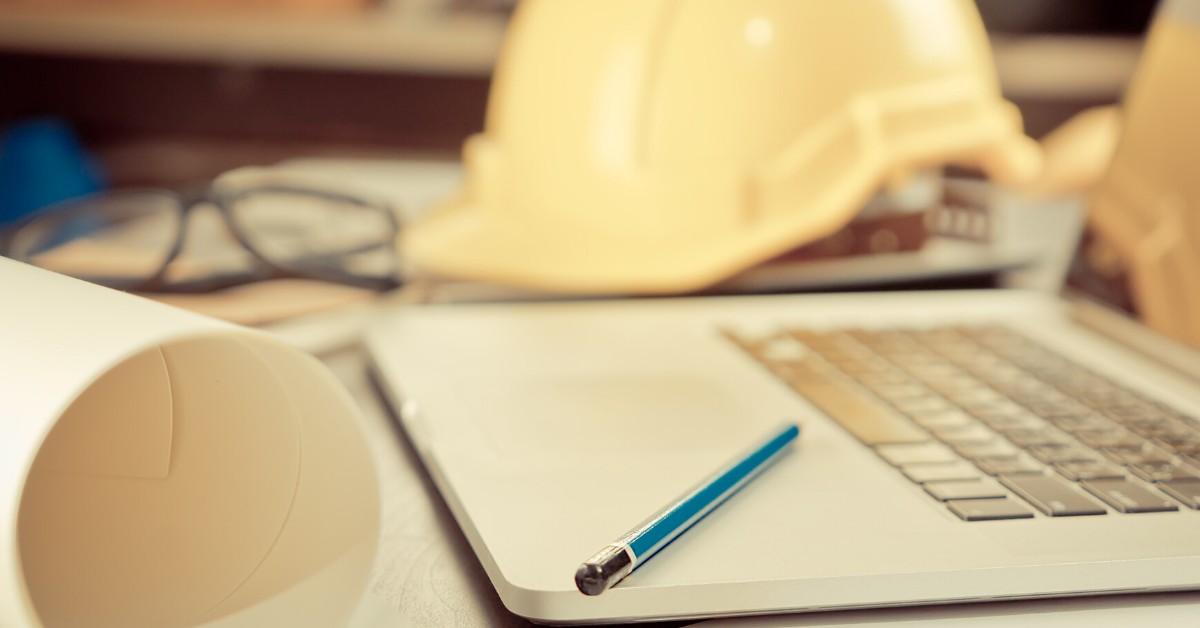 Hard hat, computer and pen on a desk