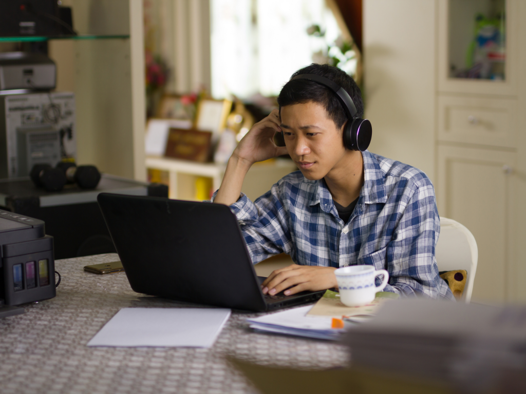 Home studying during a pandemic. Image: Asian student with headphones on whilst using a laptop.