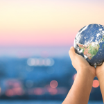 Hand holding a globe over a blurry scenescape